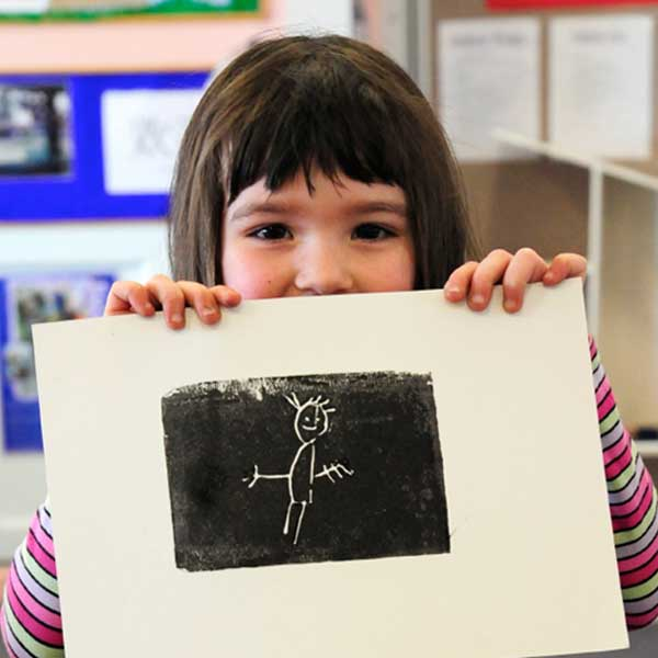 A young girl presenting her painting in an Artkids workshop