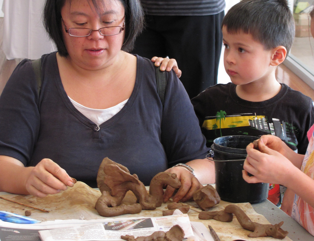 Adults and Children making pots out of clay