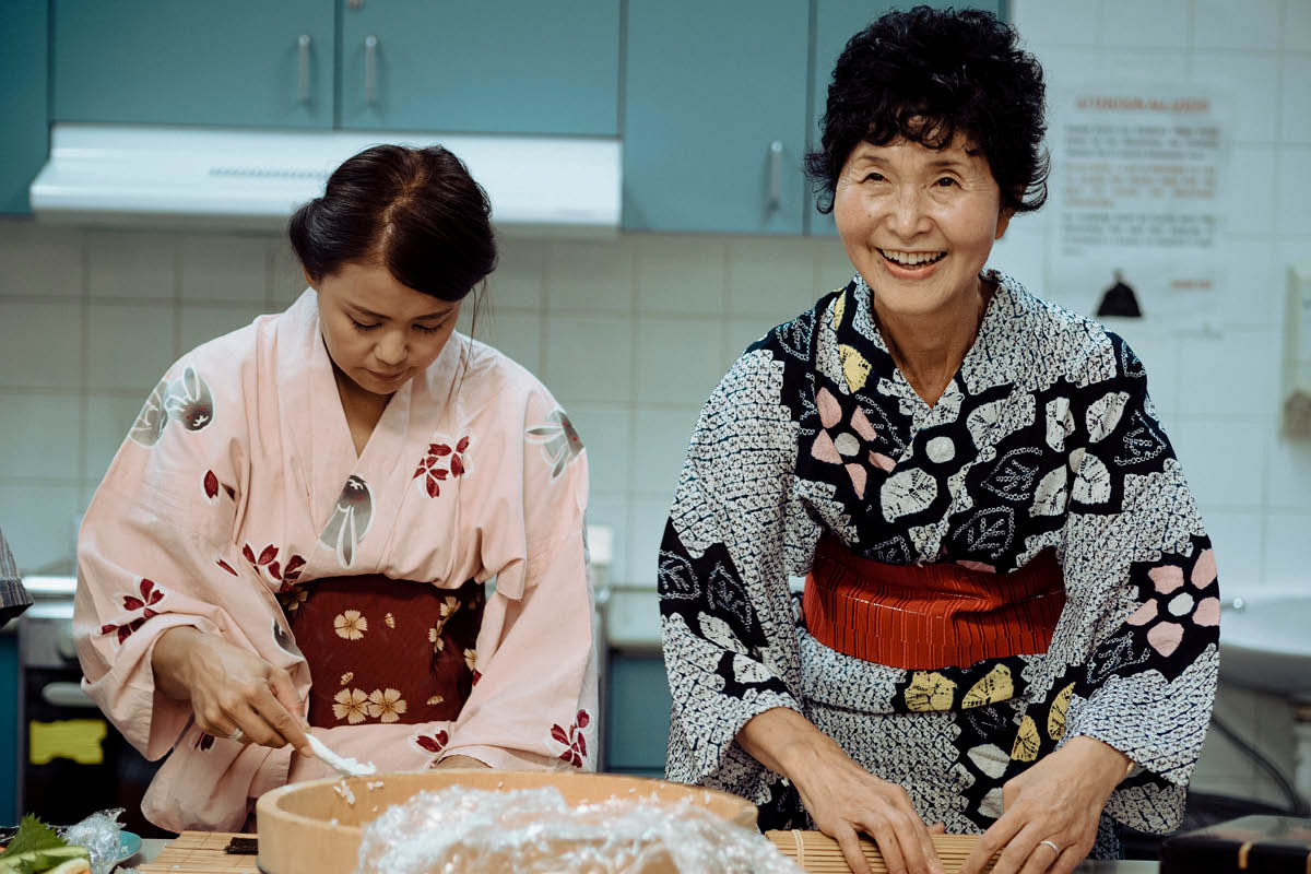 Two Japanese ladies in kimonos preparing food